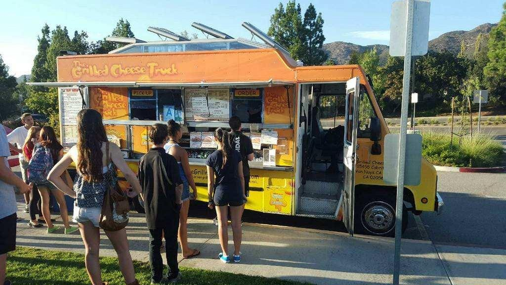 Students wait in line to buy food from The Grilled Cheese Truck Oct. 2. Athletic Booster Club Chair Julie Ahdoot said she is concerned that food trucks like this one will reduce snack shack sales, which fund the ABC (Nick Burt/Talon).