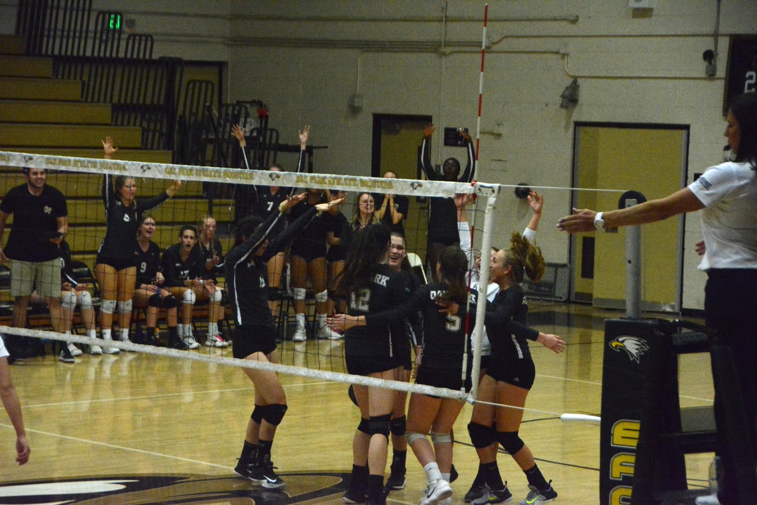 Girls' varsity volleyball team spikes the ball over the net in order to get ahead in the game