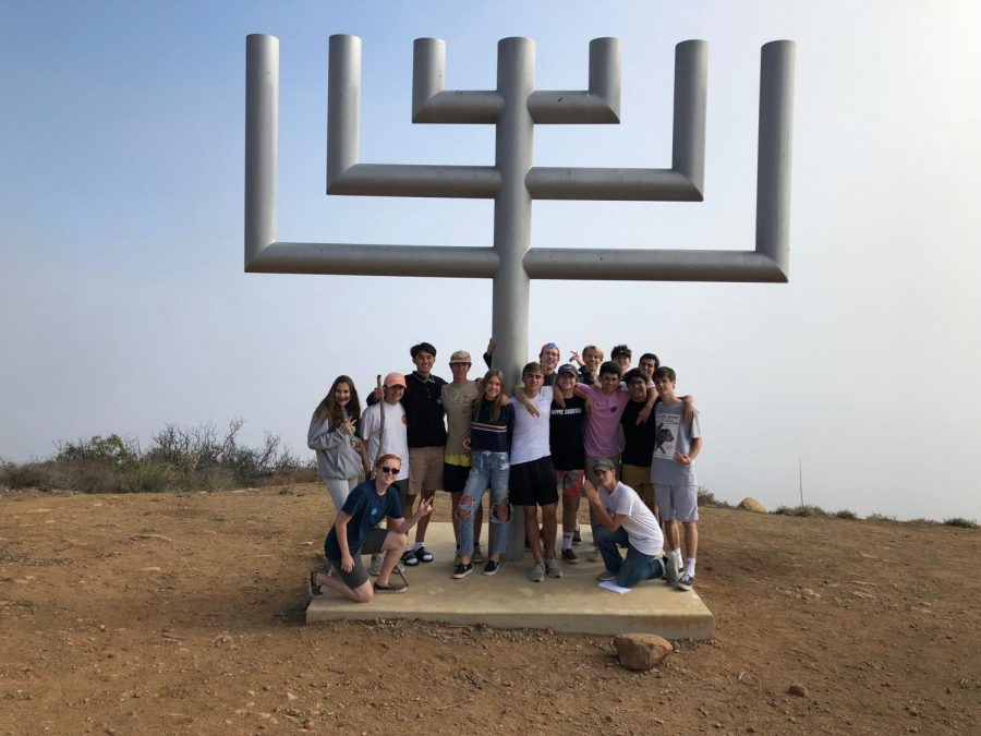 Students+gather+around+the+menorah%2C+which+stills+stands+after+the+campsite+burned+in+Malibu+during+the+Woolsey+Fire
