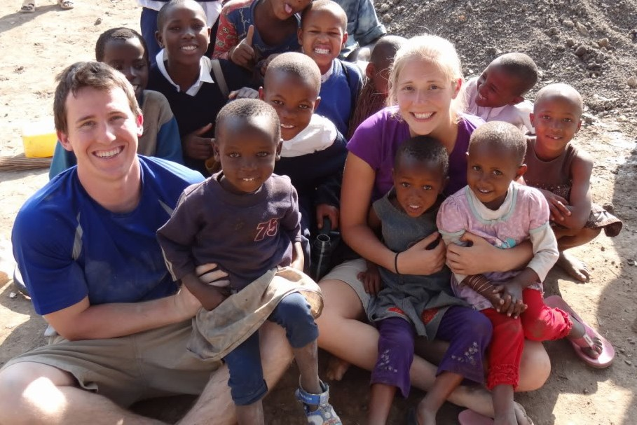 Callahan and his wife Alyssa pose in Tanzania with primary school children.