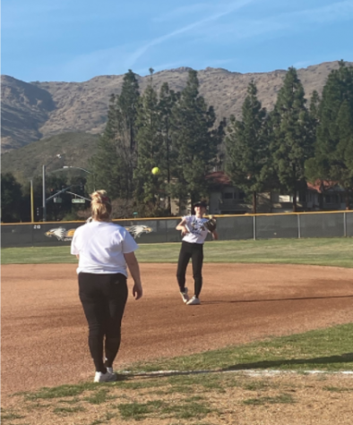 Senior co captains Aubrey Billig and Havi Rubenfeld warm up together in preparation for upcoming softball games.